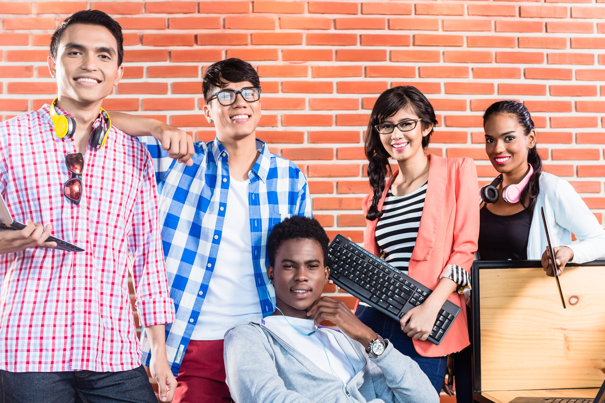 Diverse group of people with tech accessories in tech workplace smiling Bridging the diversity gap in tech