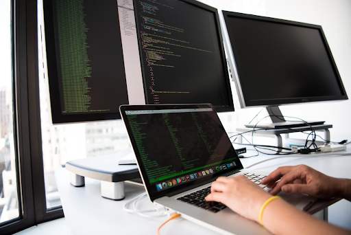 Someone typing code into a laptop in front of two desktop monitors to develop software.