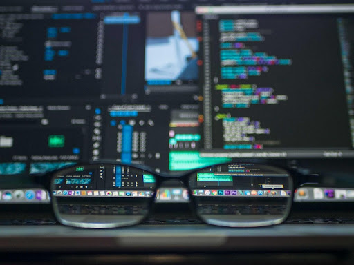 Glasses sitting in front of a laptop showing code.