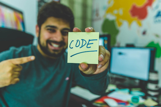 """A smiling man holding up and pointing to a sticky note reading """"Code."""""""