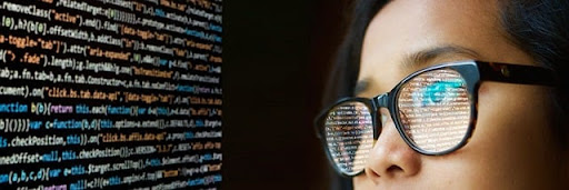 girl looking at code with reflection in glasses