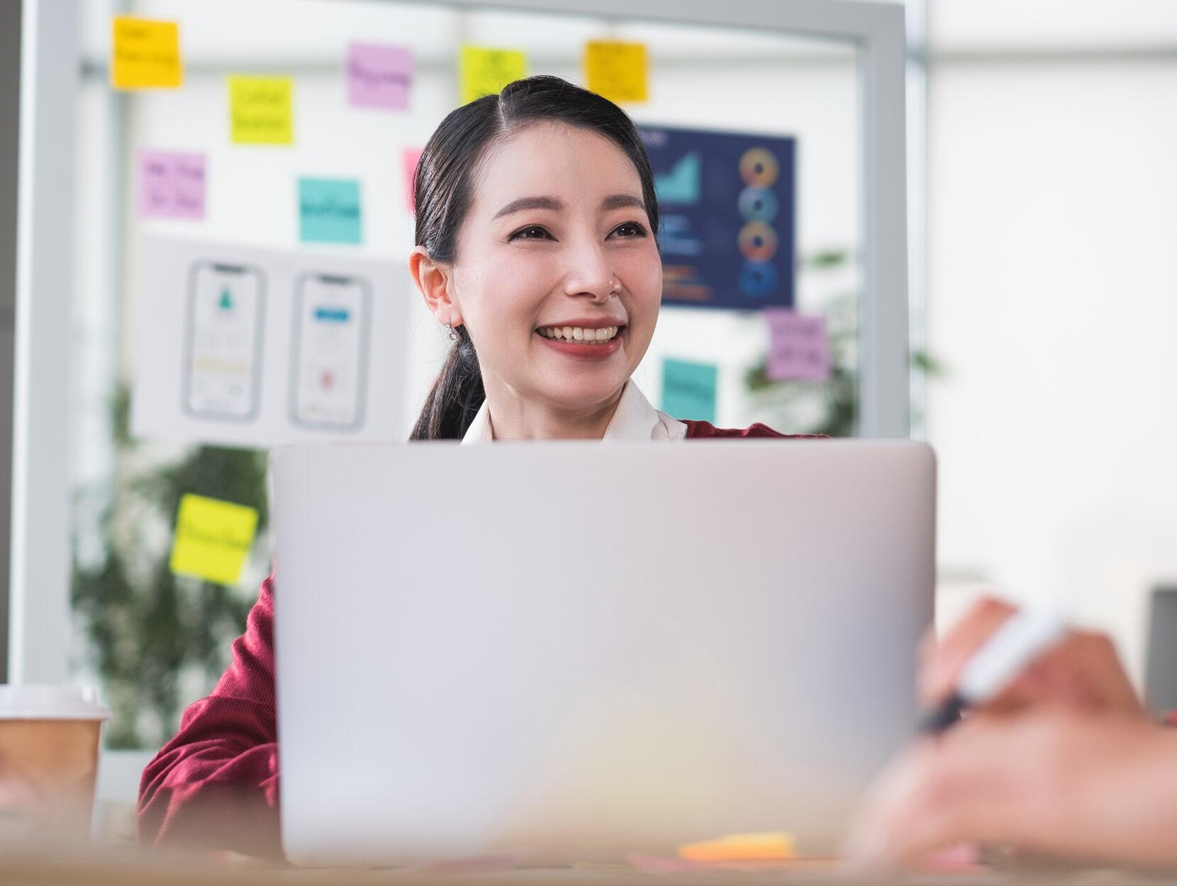 Female Web Developer Smiling At Work On Laptop Tech Job Interview