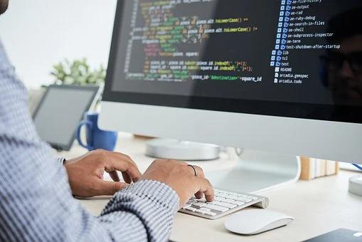A software developer typing code into a desktop computer.