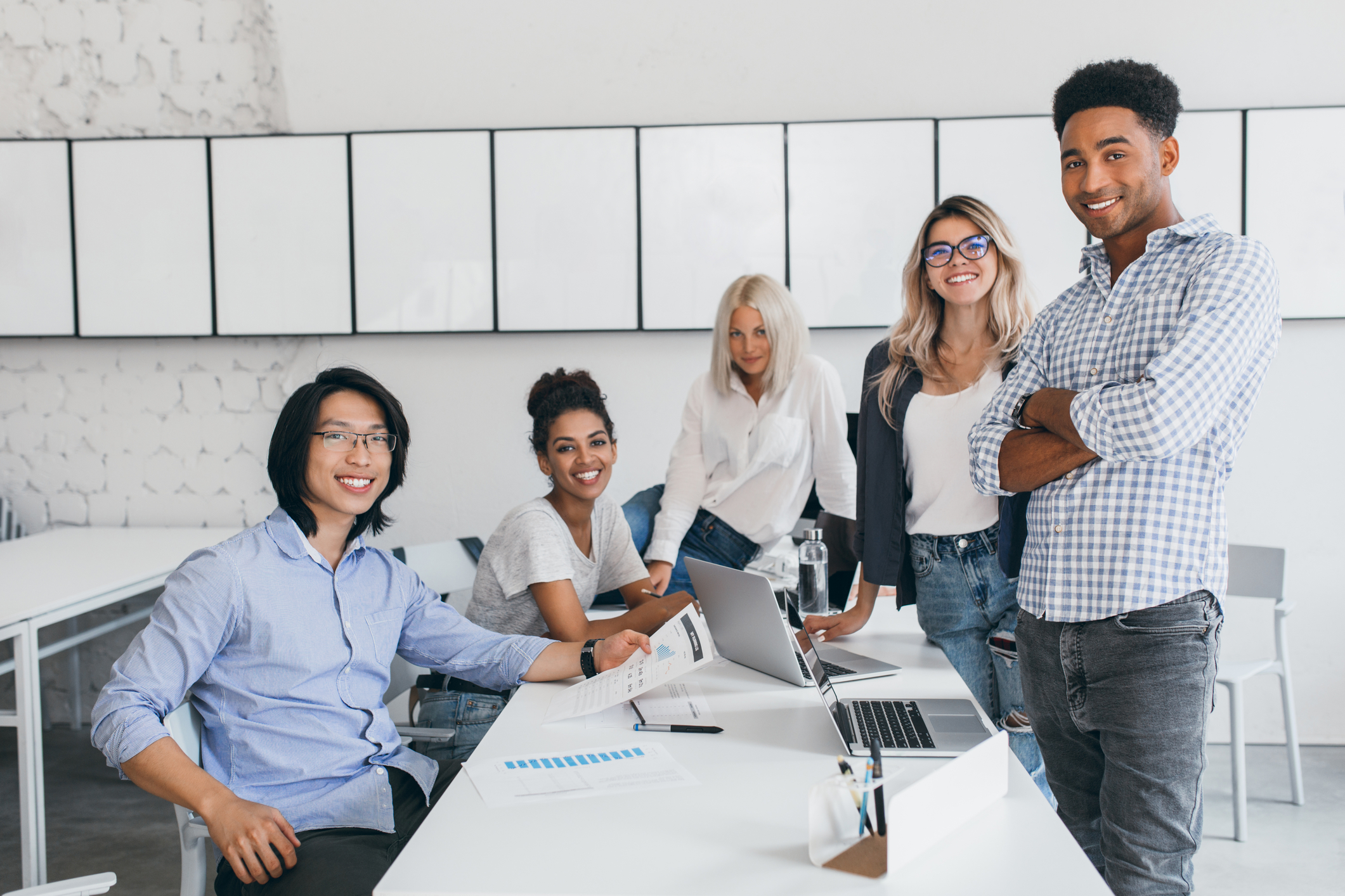 Diverse people working together on computers at a table in office Bridging the diversity gap in tech
