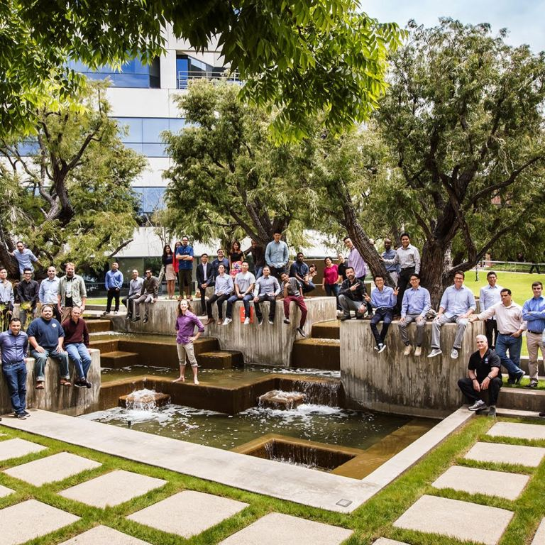 Sabio Staff and Fellows group photo outside around fountain with trees and building in background great tech job