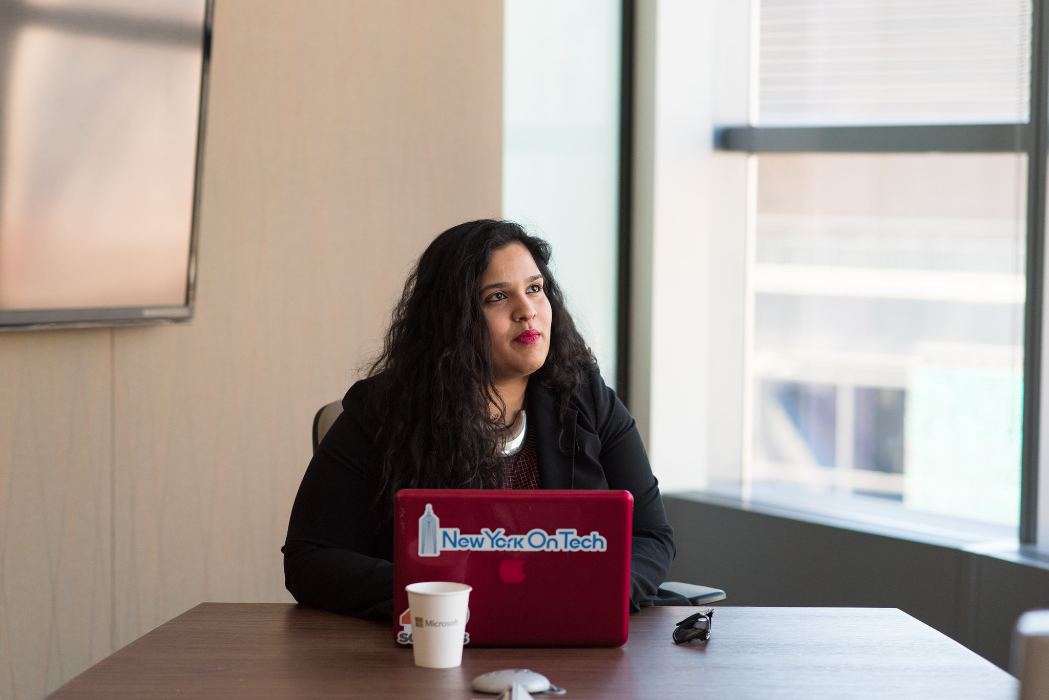 Web Developers Salary WOCinTechChat.com latino woman working in office with coffee cup and laptop on table