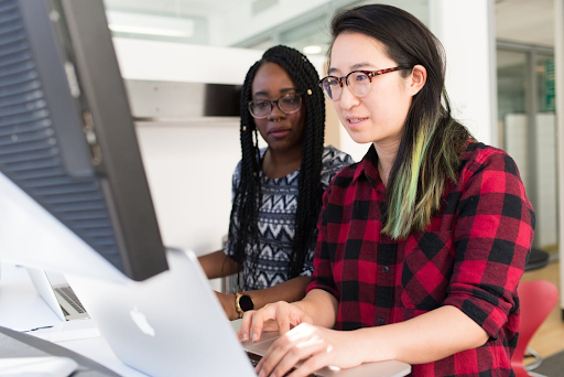 Two women software developers working together at a computer.
