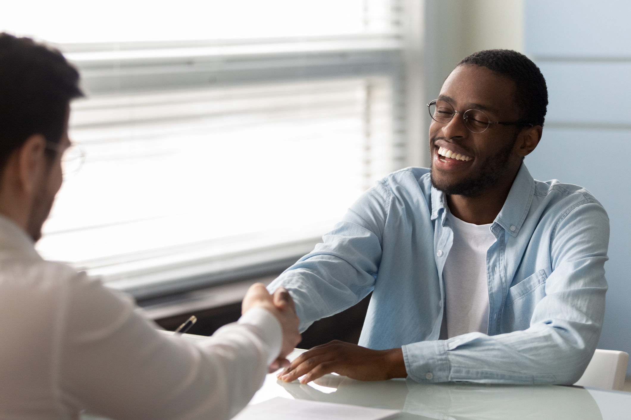 Boss and Interviewee shaking hands after applicant accepts job offer and is hired Job as a Web Developer