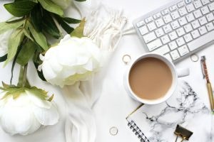 Pretty white desk with a white flower next to a laptop keyboard and coffee cup